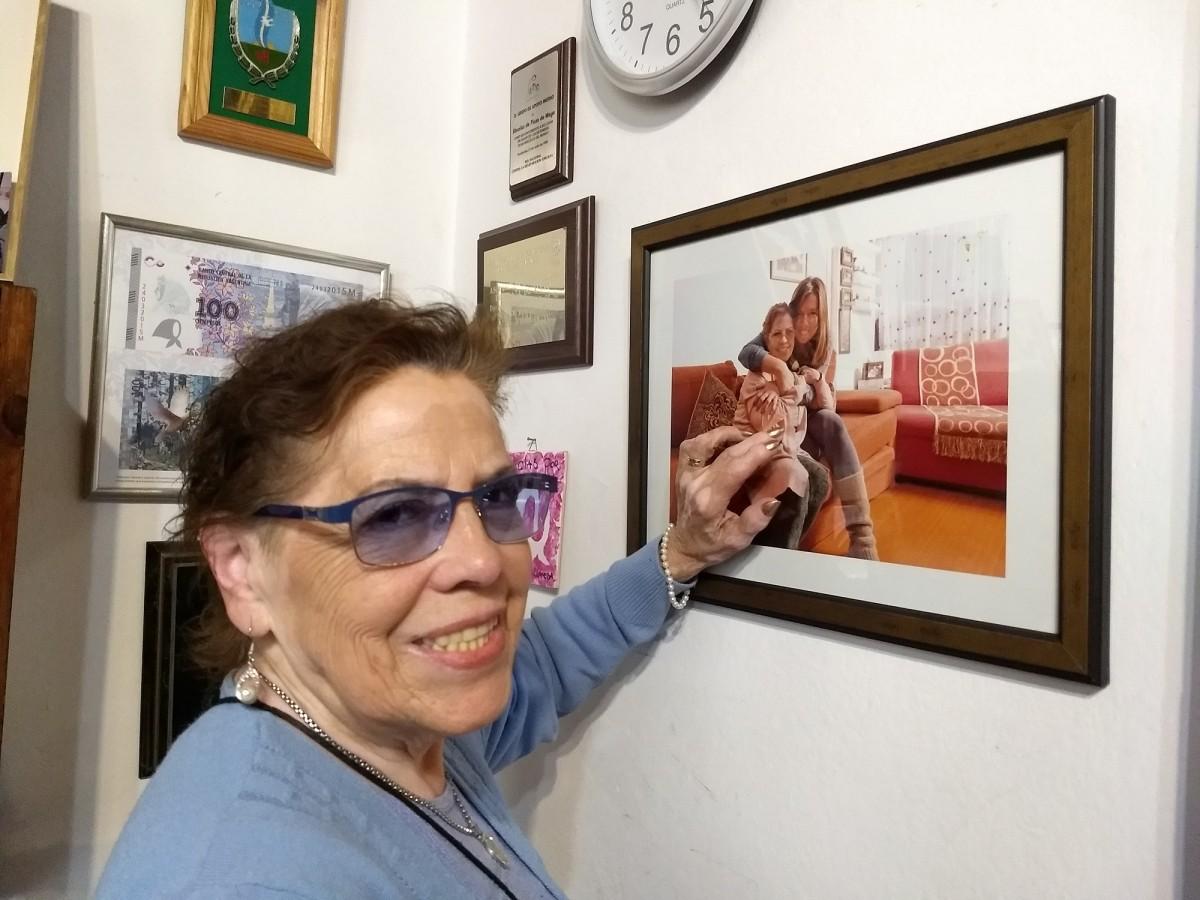 Buscarita Roa mostra a foto emoldurada na sede das Avós da Praça de Maio, em Buenos Aires, onde aparece abraçada à neta Claudia | Foto: Aline Gatto Boueri